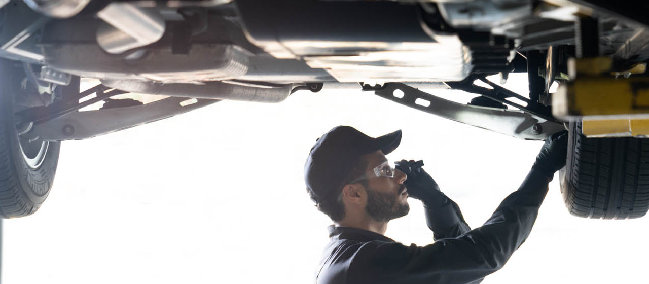 GM Genuine Parts Technician Inspecting Underside of a Vehicle